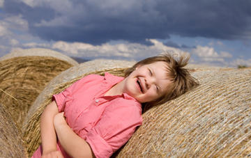 Girl learning against straw bale photo